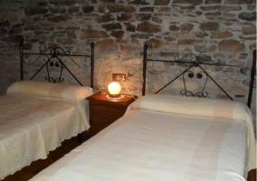 Dormitorio doble con dos camas individuales, pared de piedra y madera de la casa rural