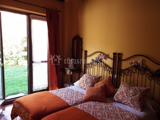 Dormitorio con camas dobles y acceso al jardín