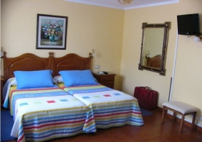 Habitación con 2 camas individuales y televisión en la pared