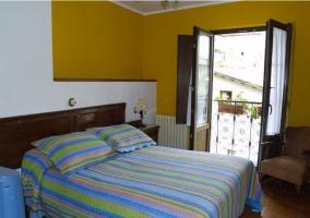 Habitación con cama matrimonial y balcón