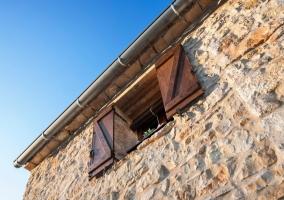 Detalle de ventana de madera en la fachada de piedra