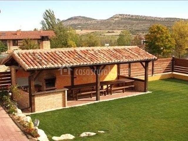 porche techado con barbacoa bancos de madera y jardn