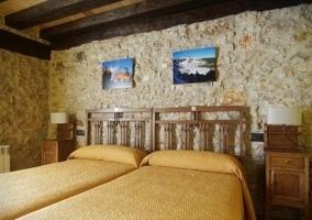 Dormitorio doble con baño privado y decoración en tonos rojizos y piedra