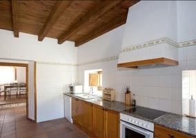 Cocina con armarios de madera y mesa con sillas