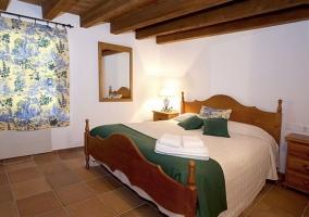 Dormitorio con colchas en blanco y mantas verdes