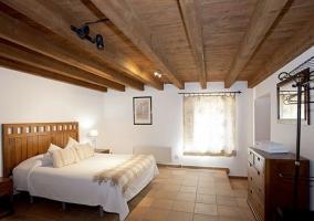 Dormitorio de matrimonio con perchero y cabeceros de madera