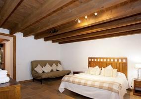 Dormitorio de matrimonio con techos de madera y muebles