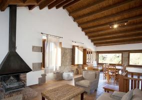 Sala de estar con chimenea y sillones en color crudo