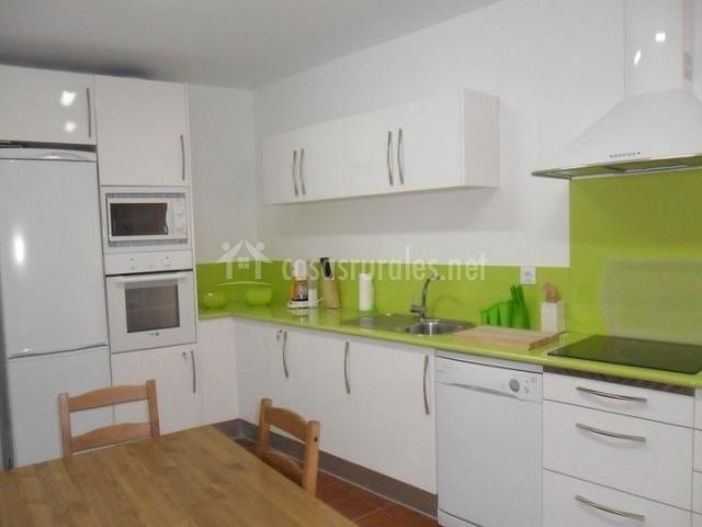 Cocina en blanco y verde con mesa de madera