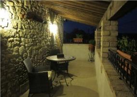 Porche de piedra con mesa y sillas casa rural