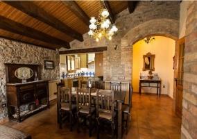 Salón-comedor con paredes de piedra y mobiliario de madera oscura