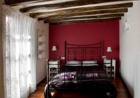 Dormitorio de matrimonio con pared roja y cabecero de hierro
