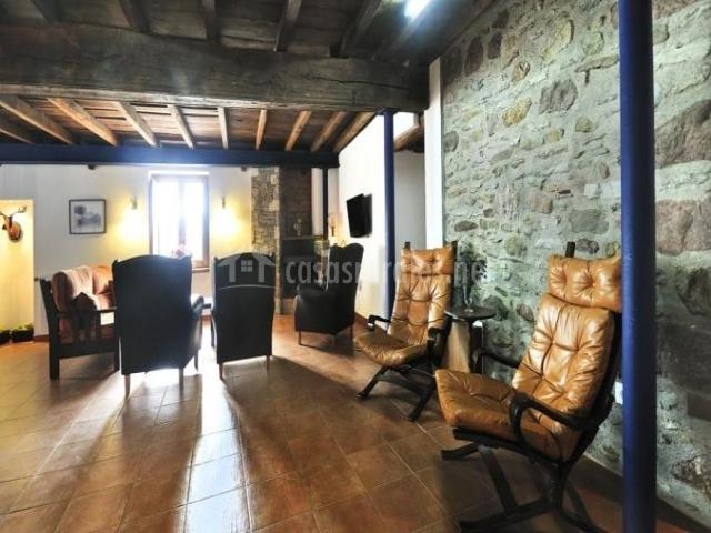Butacas y sillón en el salón con chimenea y paredes de piedra
