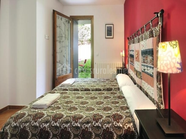 Dormitorio con camas individuales y salida al patio exterior