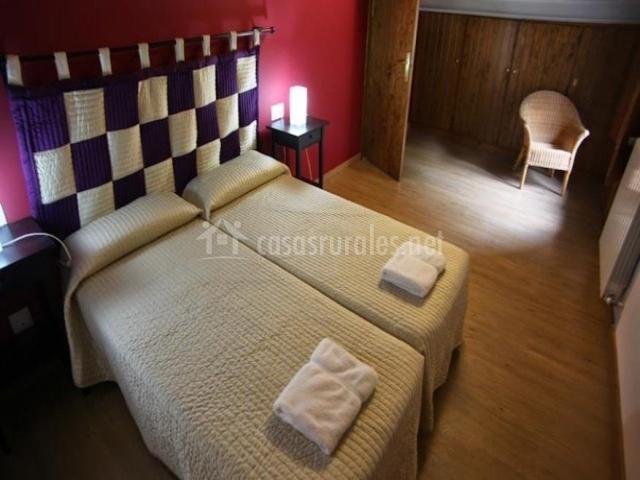Dormitorio con dos camas individuales y cabecero de tela
