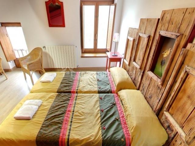 Dormitorio con dos camas y cabecero con tablas de madera
