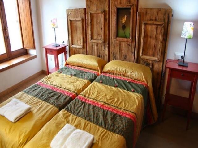 Dormitorio con dos camas y cabecero de maderas