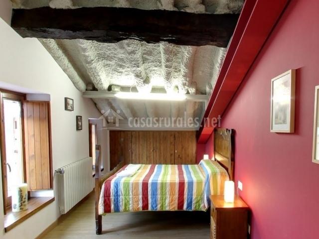 Dormitorio de matrimonio con colcha de colores y pared roja
