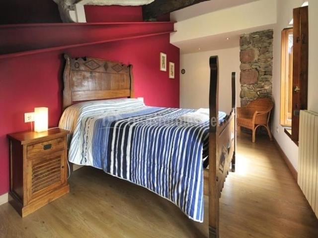 Dormitorio de matrimonio con pared roja y techo abuhardillado