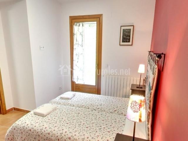 Dormitorio doble con camas individuales y pared roja