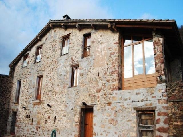 Fachada del alojamiento con piedras y ventanas