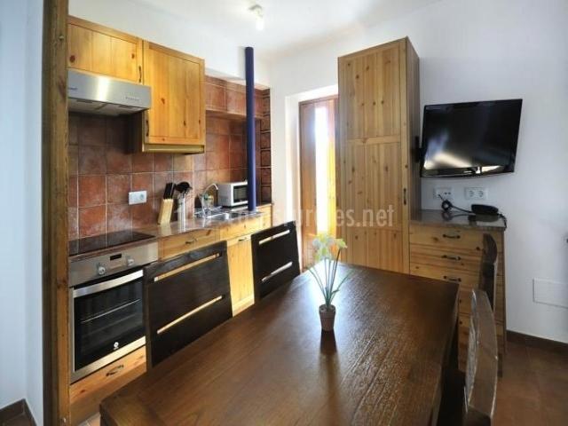 Mesa de comedor delante del televisor y junto a la cocina