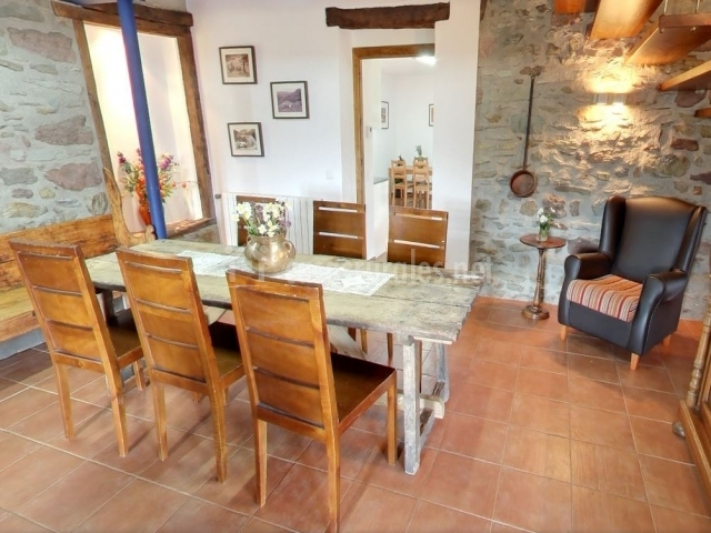 Mesa del comedor principal con sillas y acceso a la cocina