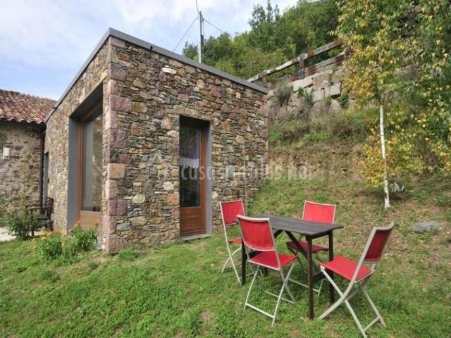 Patio exterior con hierba y muebles de jardín
