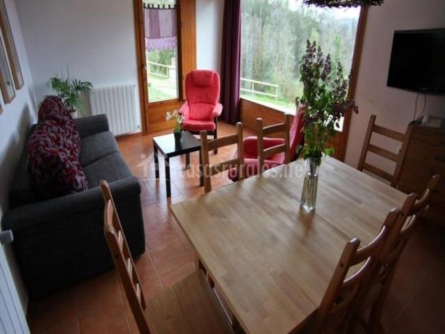 Salón comedor con mesa y sillones junto a cristalera