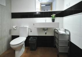 Aseo con inodoro y lavabo junto a toallero