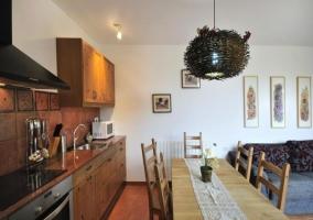 Cocina con horno delante de la mesa del comedor y junto al salón