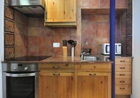 Cocina con muebles de madera y microondas
