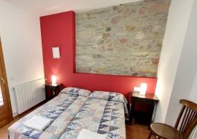 Dormitorio con dos camas individuales y pared de piedras