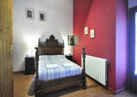Dormitorio de matrimonio con cabecero oscuro y pared roja