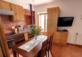 Mesa de comedor junto al televisor y la cocina