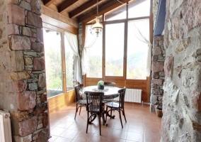 Mesa redonda con sillas junto a cristalera a la entrada de la casa