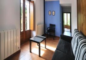 Salón con sillón oscuro y mesa baja delante
