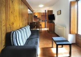 Sillón del salón con pared de madera y comedor cocina al fondo