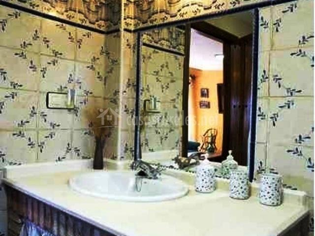 Cuarto de baño con azulejos y espejo. Lavabo