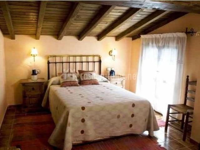 Dormitorio de matrimonio con vigas de madera. Tonos marrones