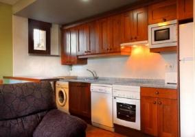 Salón comedor con sillón y cocina abierta en la misma estancia