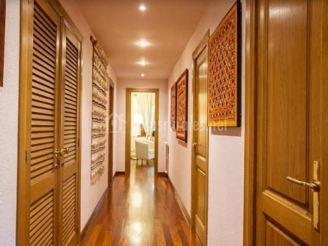 Pasillo distribuidor de la casa con suelo de madera