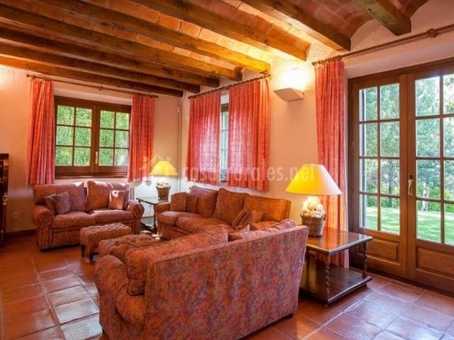 Sala de estar con sillones tapizados y puertas acristaladas