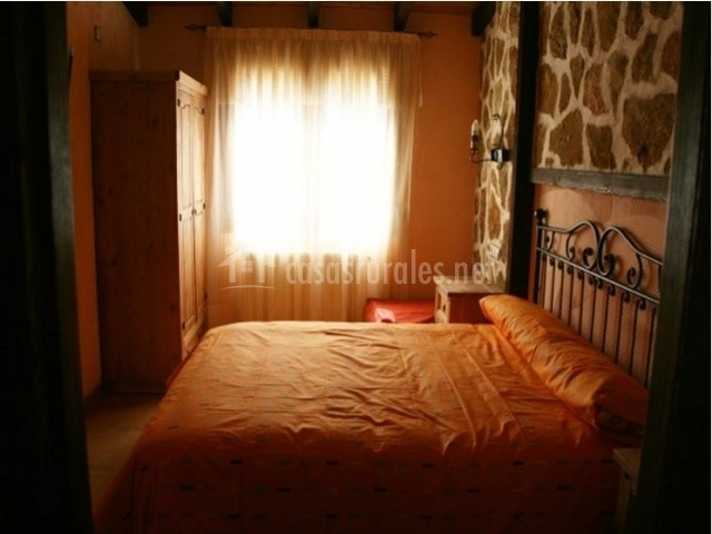Dormitorio naranja con armario y cabecero