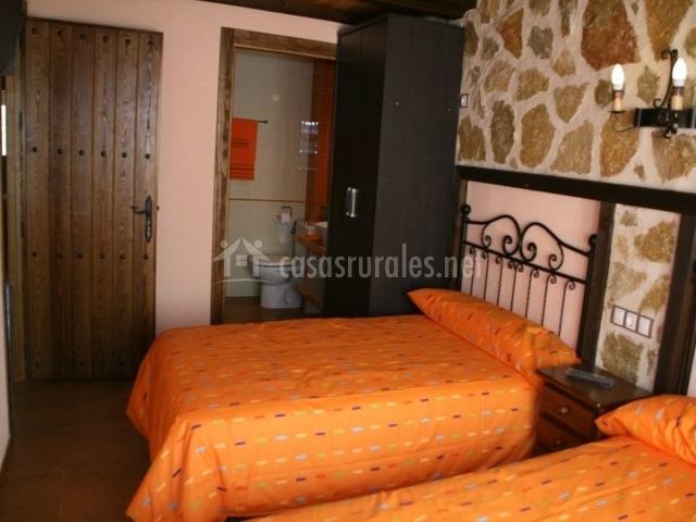 Dormitorio con dos camas naranja
