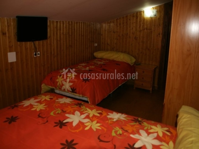 Dormitorio de madera con dos camas