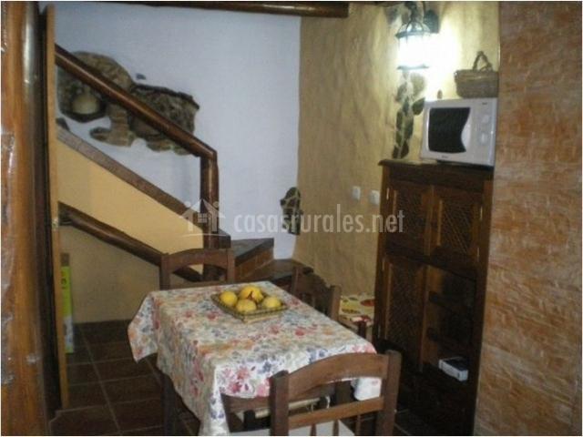 Cocina con mesa de comedor y escaleras al fondo