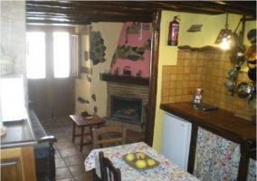 Cocina con mesa de comedor y salon con chimenea