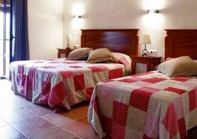 Habitación doble de la casa rural con amplias camas y una terraza
