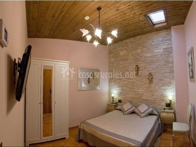 dormitorio matrimonial con lmpara muy original en el techo en casa rural